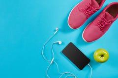 Configuration plate tirée de l'équipement de sport Espadrilles, écouteurs et téléphone sur le fond bleu Image libre de droits