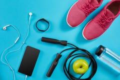 Configuration plate tirée de l'équipement de sport Espadrilles, corde de saut, écouteurs et téléphone sur le fond bleu Photo stock