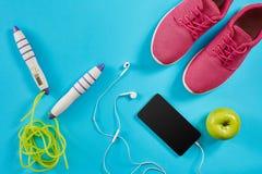 Configuration plate tirée de l'équipement de sport Espadrilles, corde de saut, écouteurs et téléphone sur le fond bleu Images libres de droits