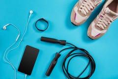 Configuration plate tirée de l'équipement de sport Espadrilles, corde de saut, écouteurs et téléphone sur le fond bleu Photographie stock