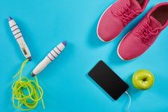 Configuration plate tirée de l'équipement de sport Espadrilles, corde de saut, écouteurs et téléphone sur le fond bleu Photo libre de droits