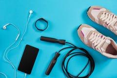Configuration plate tirée de l'équipement de sport Espadrilles, corde de saut, écouteurs et téléphone sur le fond bleu Image libre de droits