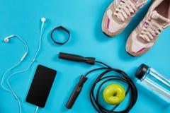 Configuration plate tirée de l'équipement de sport Espadrilles, corde de saut, écouteurs et téléphone sur le fond bleu Photos stock