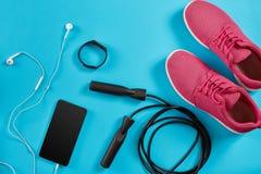 Configuration plate tirée de l'équipement de sport Espadrilles, corde de saut, écouteurs et téléphone sur le fond bleu Photos libres de droits