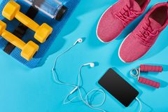 Configuration plate tirée de l'équipement de sport Espadrilles, eau, écouteurs et téléphone sur le fond bleu Image stock
