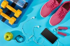 Configuration plate tirée de l'équipement de sport Espadrilles, eau, écouteurs et téléphone sur le fond bleu Image libre de droits
