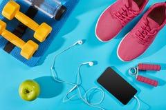 Configuration plate tirée de l'équipement de sport Espadrilles, eau, écouteurs et téléphone sur le fond bleu Photographie stock