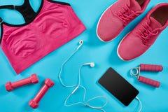 Configuration plate tirée de l'équipement de sport Espadrilles, haltères, écouteurs et téléphone sur le fond bleu Image stock