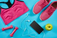 Configuration plate tirée de l'équipement de sport Espadrilles, haltères, écouteurs et téléphone sur le fond bleu Image libre de droits