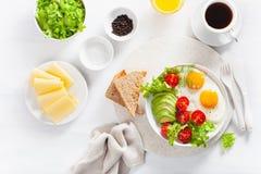Configuration saine d'appartement de petit déjeuner oeufs au plat, avocat, tomate, pains grillés Image stock