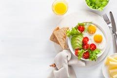 Configuration saine d'appartement de petit déjeuner oeufs au plat, avocat, tomate, pains grillés Images libres de droits