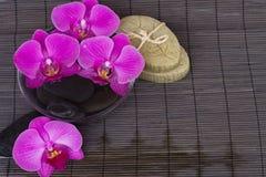 Configurations de station thermale avec des orchidées sur le couvre-tapis en bambou image libre de droits