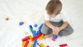 Configurazioni sveglie piccole di un ragazzo dai blocchi colorati del progettista, sedentesi sul pavimento bianco I giochi da bam stock footage