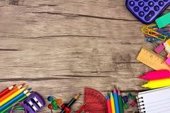 Confine d'angolo dei rifornimenti di scuola contro legno immagine stock libera da diritti