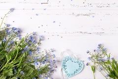 Confine dai nontiscordardime o fiori e cuore blu del miosotis immagine stock
