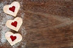 Confine dei biscotti del cuore di giorno di biglietti di S. Valentino con zucchero in polvere sopra legno Fotografia Stock