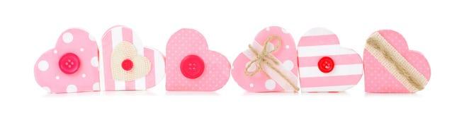 Confine dei contenitori di regalo in forma di cuore dei biglietti di S. Valentino rosa rustici sopra bianco Immagini Stock