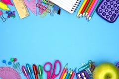 Confine dei rifornimenti di scuola doppio contro il blu Fotografia Stock Libera da Diritti