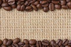 Confine del caffè Fagioli sopra il fondo della tela da imballaggio fotografia stock libera da diritti