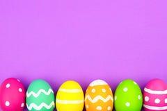 Confine del fondo dell'uovo di Pasqua sopra fondo di carta porpora Fotografia Stock Libera da Diritti