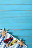 Confine del fondo della spiaggia di estate, occhiali da sole, asciugamano, stella marina, spazio di legno blu della copia, vertic Immagine Stock Libera da Diritti