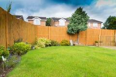 Confine del giardino con la recinzione e gli arbusti Fotografie Stock