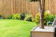 Confine del giardino con la recinzione l'erba degli arbusti e della decorazione generale del giardino Immagini Stock Libere da Diritti