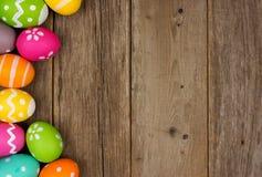 Confine del lato dell'uovo di Pasqua contro legno rustico Fotografia Stock