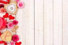 Confine del lato di giorno di biglietti di S. Valentino dei cuori, dei fiori, dei regali e della decorazione su legno bianco Fotografie Stock