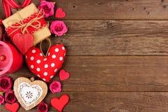 Confine del lato di giorno di biglietti di S. Valentino dei cuori, dei regali, dei fiori e della decorazione su legno rustico Fotografia Stock