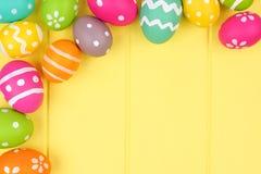 Confine dell'angolo dell'uovo di Pasqua contro legno giallo Fotografia Stock
