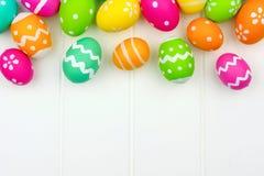 Confine della cima dell'uovo di Pasqua contro legno bianco Immagine Stock