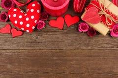 Confine della cima di giorno di biglietti di S. Valentino dei cuori, dei regali, dei fiori e della decorazione su legno rustico Immagini Stock