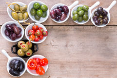 Confine delle olive e dei peperoni su un contatore di legno Immagine Stock