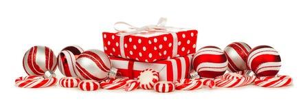 Confine di natale bianco e di rosso con i regali, le bagattelle e la caramella Immagini Stock