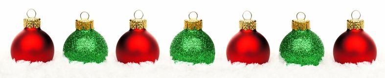 Confine di Natale delle bagattelle rosse e verdi in neve isolata Fotografie Stock Libere da Diritti