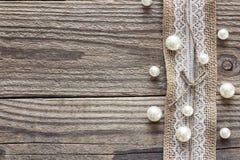 Confine di tela da imballaggio con pizzo bianco e delle perle sulla vecchia tavola di legno immagini stock