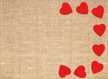 Confine el marco de corazones rojos en el texto del fondo de la arpillera de la lona del saco Imagen de archivo libre de regalías