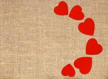 Confine el marco de corazones rojos en la arpillera de la lona del saco Foto de archivo