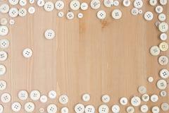 Confine fatto dei bottoni d'annata bianchi su fondo di legno Fotografie Stock