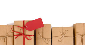Confine la fila de los paquetes del papel marrón, una única con el arco rojo de la cinta y la etiqueta del regalo Fotos de archivo libres de regalías