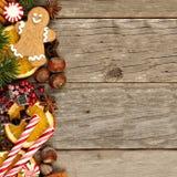 Confine laterale del Natale decorazione ed ossequi sopra legno rustico fotografia stock