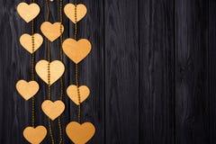 Confine piano di disposizione dei cuori e delle perle dorati Decorazione festiva su un legno nero Fotografia Stock Libera da Diritti