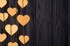 Confine piano di disposizione dei cuori e delle perle dorati Decorazione festiva su un legno nero Immagini Stock Libere da Diritti