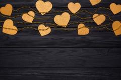 Confine piano di disposizione dei cuori e delle perle dorati Decorazione festiva sul nero di legno Fotografie Stock