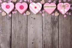Confine rustico della cima di giorno di biglietti di S. Valentino con i contenitori di regalo in forma di cuore rosa Fotografie Stock