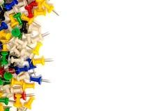 Confine sinistro di multicolore dei perni di spinta su fondo bianco Fotografia Stock Libera da Diritti