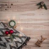 Confine stagionale di Natale composto di regali, di cervi, di candela e di sciarpa decorativi, ornamenti dei rami del pino sopra  fotografia stock