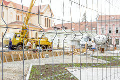 Confined space around building site. View on the pump crane for lifting and casting concrete at construction site through a fence wire with quadratic shape stock photography