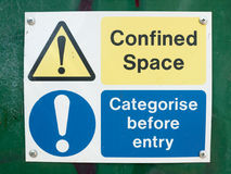 Confined space categorise before entry sign board on box. A photograph of typical signs warning of danger on a building site box stock photo